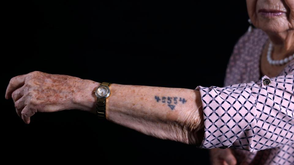 "Dagan shows her arm with the Auschwitz prison number 45554. An educator and psychologist, she has written six books about the Holocaust of which five are for children. ""I don't only recount the horror of the Holocaust, but also wonderful things like helping each other, the capacity to share a piece of bread, the friendship... We remained human beings,"" said Dagan. (Menahem Kahana / AFP)"