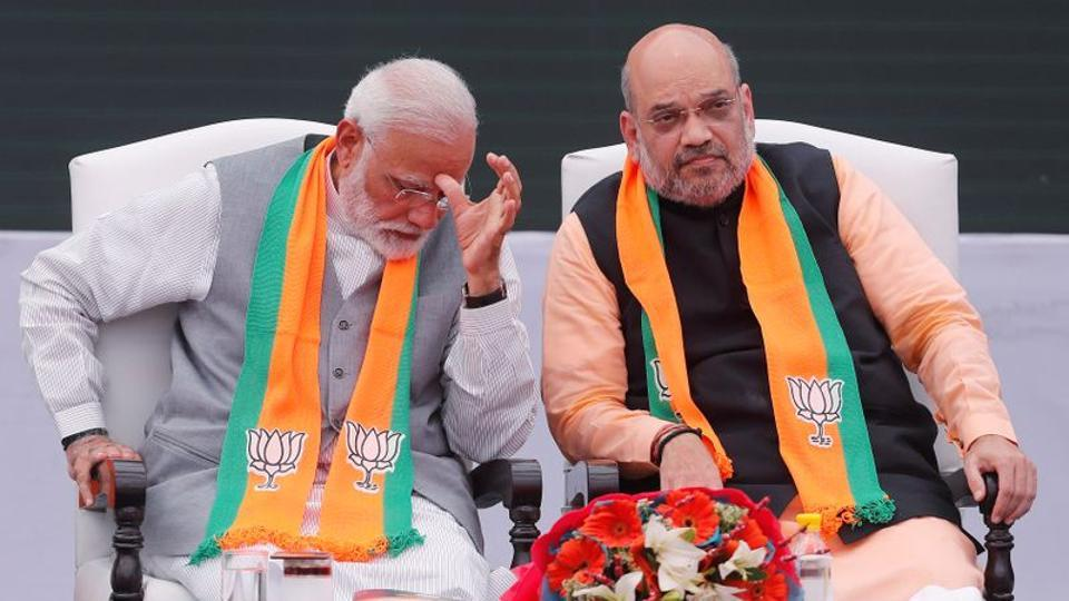 Prime Minister Narendra Modi gestures as BJP chief Amit Shah looks on after releasing their party's election manifesto for the May general election in New Delhi.
