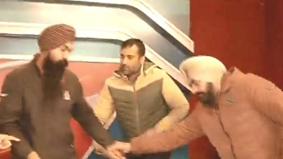Police arresting Maninder Singh (left) after barging into a news channel studio in the Industrial Area, Phase 2, Chandigarh, on Tuesday.