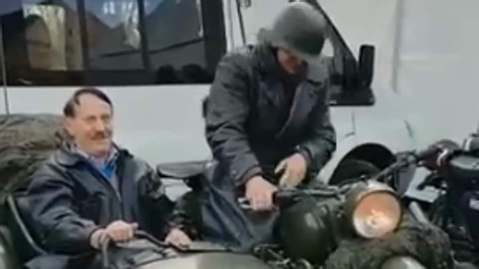 A man dressed as Adolf Hitler rode around a weekend festival in a motorbike sidecar.