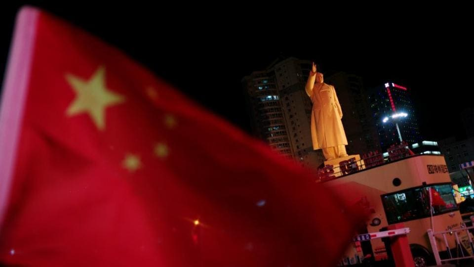 A Chinese flag flutters near a statue of late Chinese chairman Mao Zedong at a train station in Dandong, Liaoning province, in October, 2019.