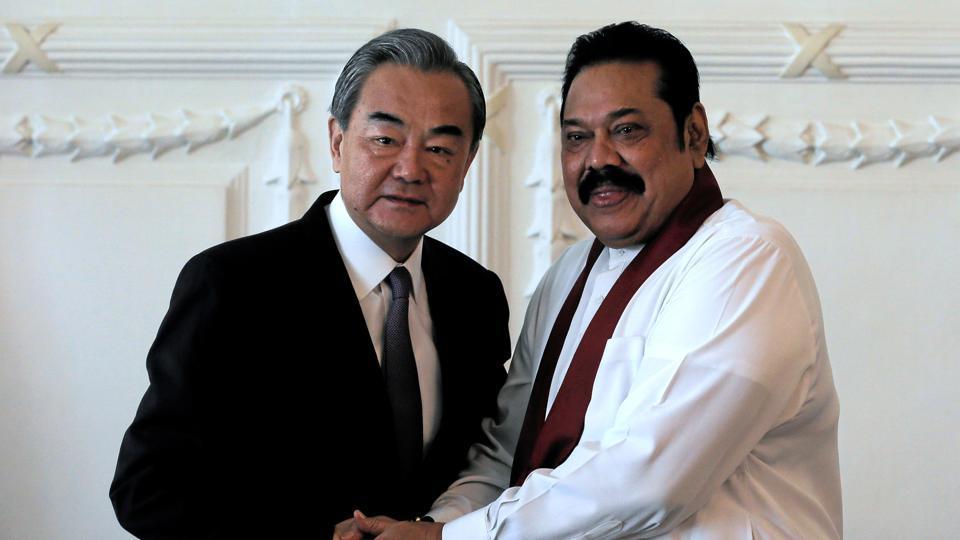 Chinese Foreign Minister Wang Yi shakes hands with Sri Lankan Prime Minister Mahinda Rajapaksa.