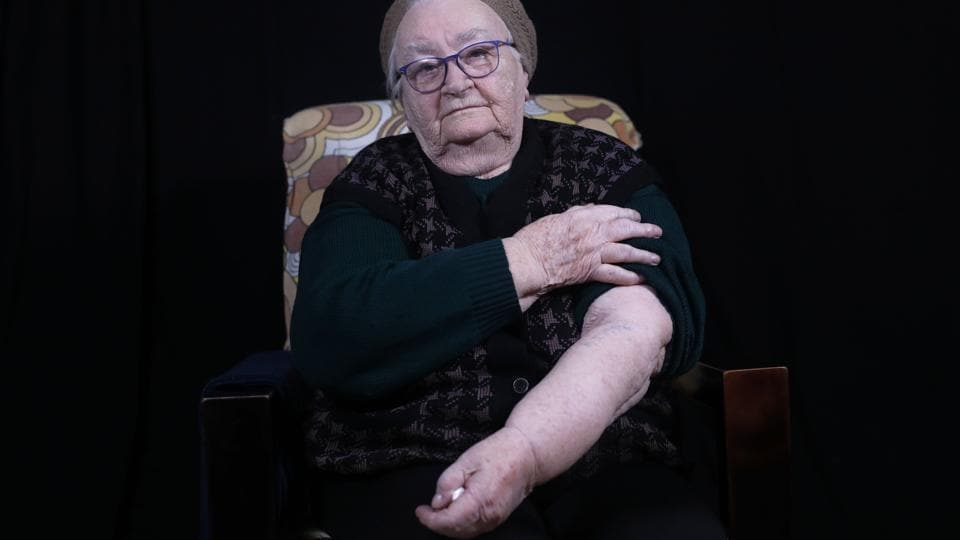 "Helena Hirsch shows her arm with the Auschwitz prison number A 20982, at her home in Israel's Beni Brak suburb east of Tel Aviv. Born in Romania in 1928, she moves around slowly with the aid of a walking frame but she maintains her lively spirit, describing herself as a 'heroine.' ""If I'm alive today, it's because I am a heroine,"" said Hirsch, the sole survivor from her family. (Menahem Kahana / AFP)"