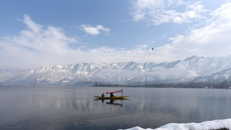 People row their boats to cross the frozen surface of Dal lake in Srinagar on 14 January 2020