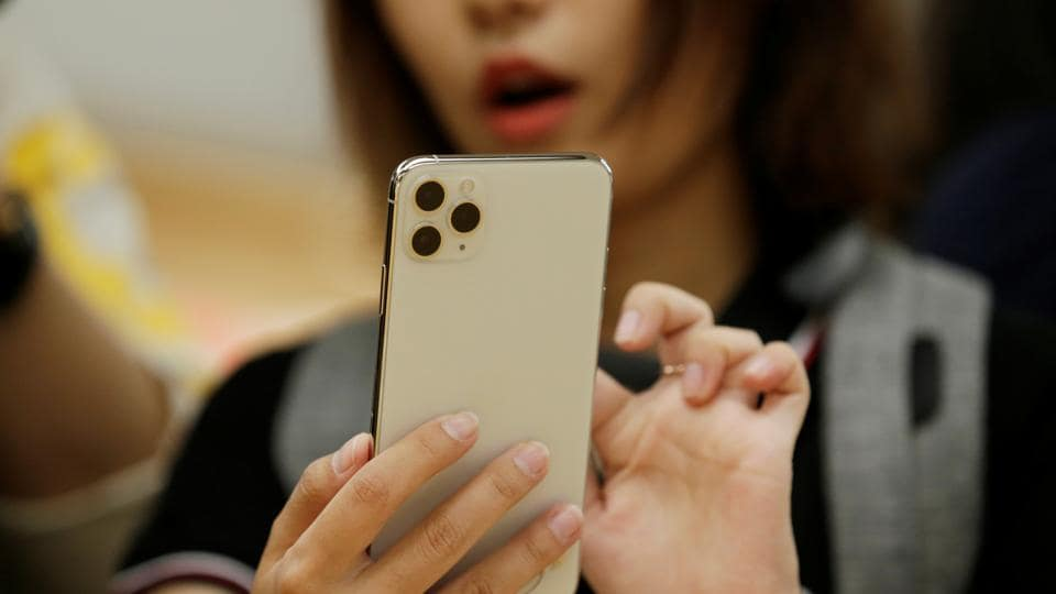 A woman holds an iPhone 11 Pro Max while giving a live broadcast after it went on sale at the Apple Store in Beijing, China, September 20, 2019.