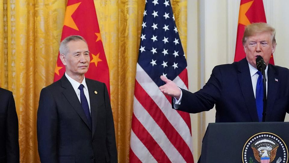 Chinese Vice Premier Liu He and his team listen to U.S. President Donald Trump as he speaks at the start of a signing ceremony for