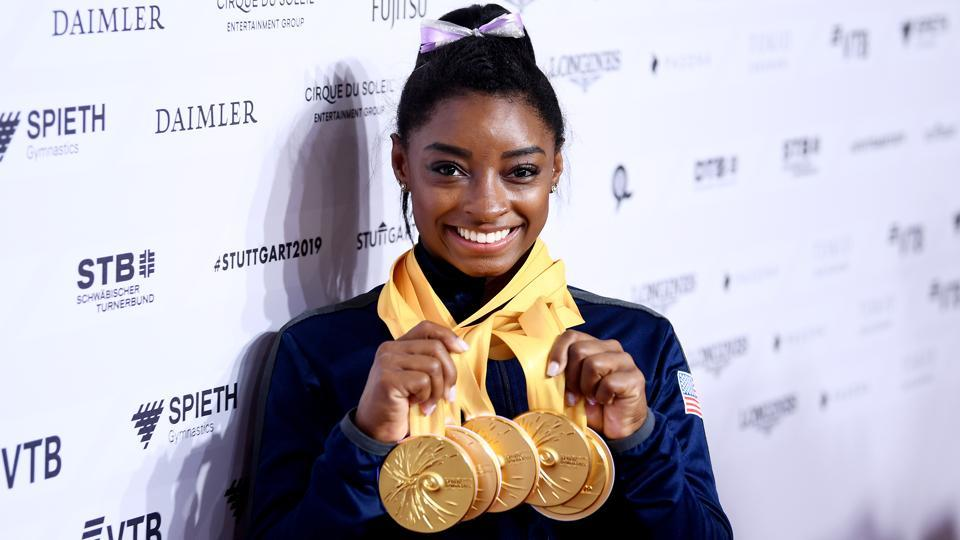 Simone Biles of The United States poses for photos with her multiple gold medals.