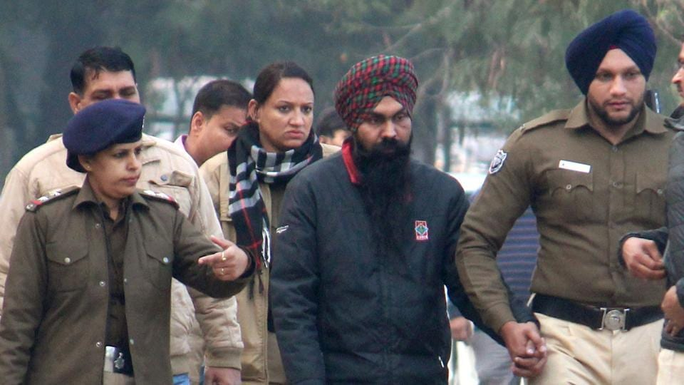 Police taking away Maninder Singh, 31, after getting his five-day custody at the district courts in Chandigarh.