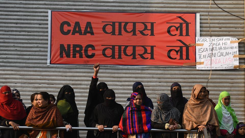 Women are seen with a banner pasted on the shutter of a closed shop during a sit-in protest against the Citizenship Amendment Act (CAA) at Shaheen Bagh. For the past month, several women in Shaheen Bagh have been living two lives—of a protester and a homemaker. They wake up in the morning, finish their chores, and come to the tent at the protest site.  (Biplov Bhuyan / HT Photo)