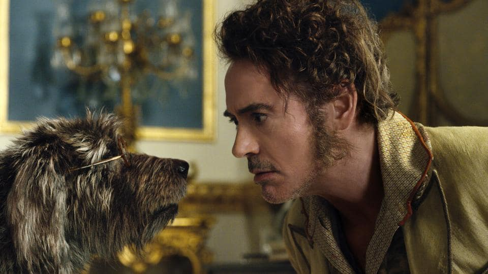 This image released by Universal Pictures shows Dr. John Dolittle, portrayed by Robert Downey Jr., right, with Jip, voiced by Tom Holland, in a scene from Dolittle.