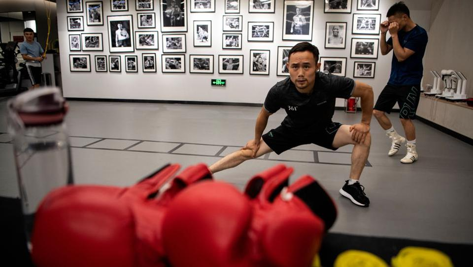 """Boxer and food delivery man, Zhang Fangyong, warming up at a boxing gym in Beijing. Unlike his idol Floyd """"Money"""" Mayweather who could earn hundreds of millions of dollars from a bout,  Zhang sometimes fights for nothing and supports himself by making deliveries on his motorbike. (Noel Celis / AFP)"""