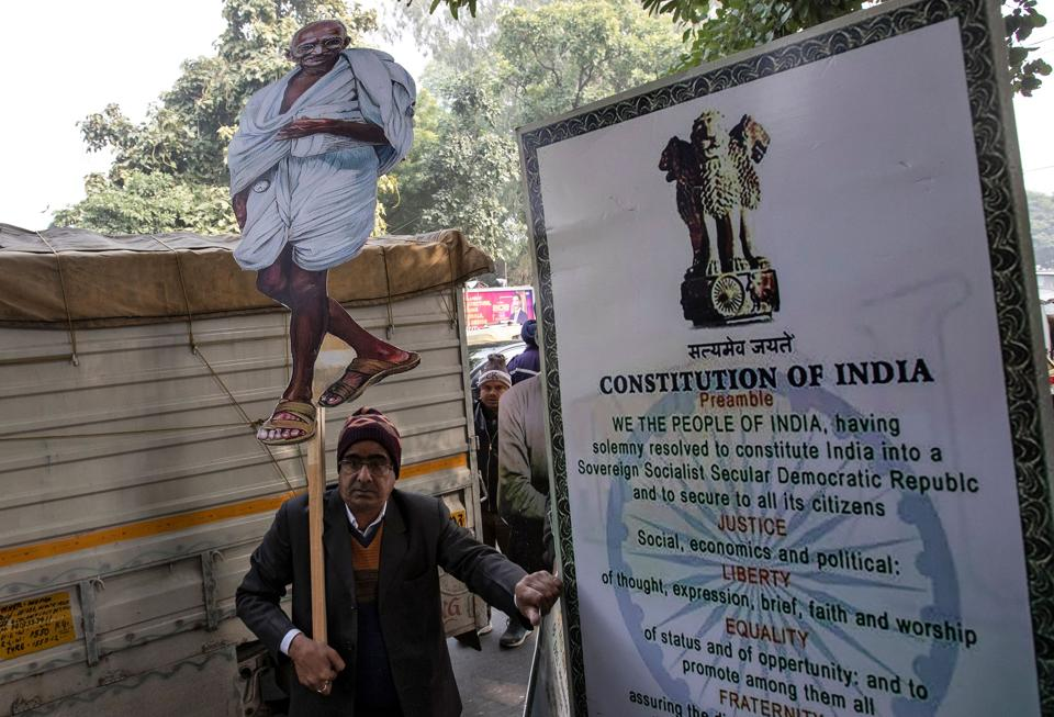 The massive protests against the CAA have brought the Constitution into the public discourse.  A demonstrator stands next to a hoarding of the Preamble to the Constitution in Delhi.