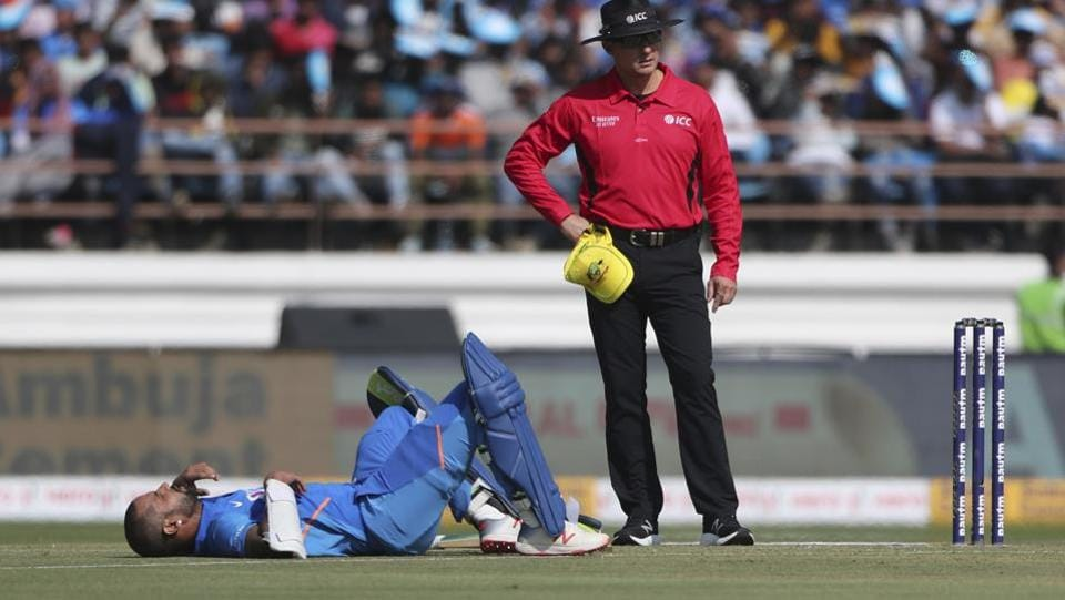 India's Shikhar Dhawan lies on the ground after being hit by a ball during the second one-day international cricket match between India and Australia in Rajkot, India, Friday, Jan. 17, 2020.