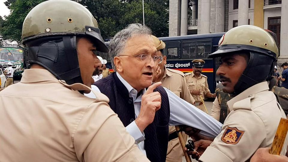Police personnel detain Indian historian Ramachandra Guha during a protest against the Citizenship Amendment Act 2019 at Townhall in Bengaluru.