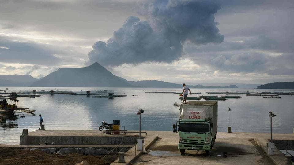 A man clears ash from the roof of his truck against a plume of steam rising from the Taal volcano, at a fishing harbour in Laurel of Batangas, Philippines. Taal is the second-most active volcano in the Philippines Islands and it began erupting on Sunday, January 12. (Ed Jones/AFP)