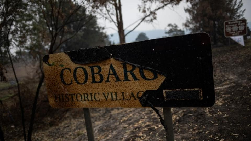 The Cobargo town sign board that was burnt during the bushfire, in New South Wales. For two weeks, builder Rod Dunn has been living at a showground in a borrowed caravan, wearing an old coat donated by a friend. His house, car, sheds and work tools were wiped out by the ferocious New Year bushfires that swept through the Australian town of Cobargo, killing three of its residents and destroying dozens of homes.  (Alkis Konstantinidis/ REUTERS)