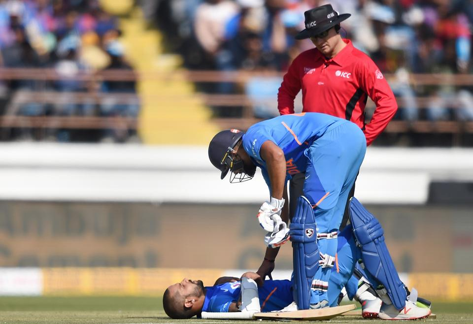 Indian batsman Shikhar Dhawan lies on the ground after being hit by the ball as Rohit Sharma watch during the second one day international (ODI) cricket match between India and Australia at Saurashtra Cricket Association Stadium in Rajkot, Friday, Jan. 17, 2020.