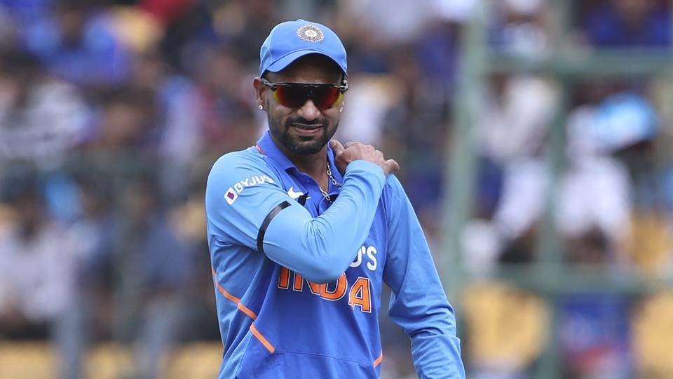 India's Shikhar Dhawan holds his shoulder as he leaves the ground after getting hurt while fielding during the third one-day international cricket match between India and Australia in Bangalore.