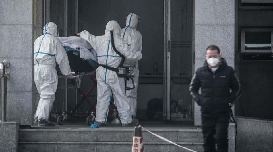 Medical staff members carry a patient into the Jinyintan hospital, where patients infected by a mysterious SARS-like virus are being treated, in Wuhan in China's central Hubei province on January 18, 2020.