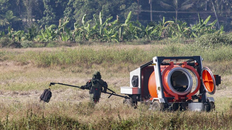 A bomb disposal squad member carries the suspicious bag, allegedly containing an IED component, for detonation after it was found at the airport in Mangaluru, Monday.