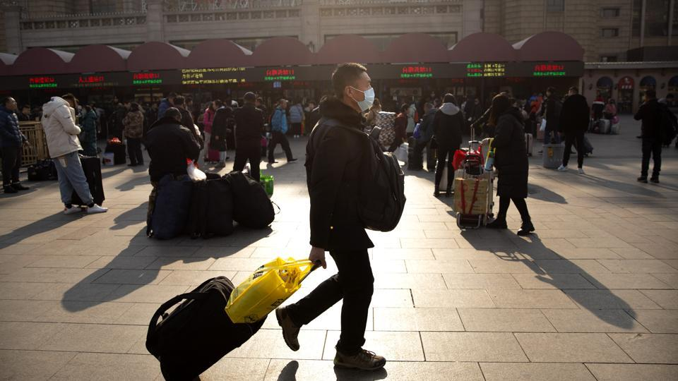 A traveller wears a facemask as he walks in front of the Beijing Railway Station on Friday.