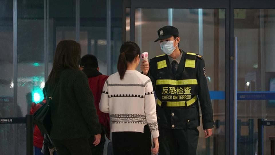 An airport staff member uses a temperature gun to check people leaving Wuhan Tianhe International Airport, January 21, 2020
