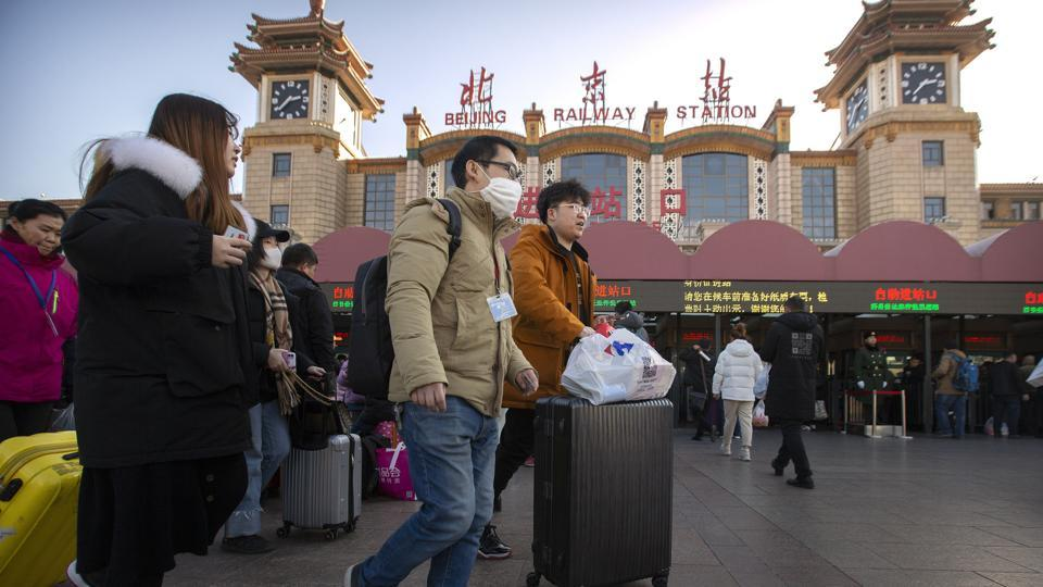 A traveller wears a face mask as he walks outside of the Beijing Railway Station in Beijing on January 20. With millions of Asians travelling on Tuesday for the Lunar New Year holiday, authorities in China confirmed that a new virus could be spread through human contact, reporting 15 medical staff had been infected and a fourth person had died. (Mark Schiefelbein / AP)