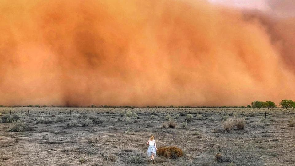 """A child runs towards a dust storm in Mullengudgery in New South Wales, Australia. Thunderstorms and giant hail battered parts of Australia's east coast on Monday after """"apocalyptic"""" dust storms swept across drought-stricken areas, as extreme weather patterns collided in the bushfire fatigued country. (Courtesy of Marcia Macmillan / AFP)"""