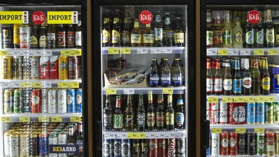 Beers and other alcoholic drinks sit on display in a refrigerator.