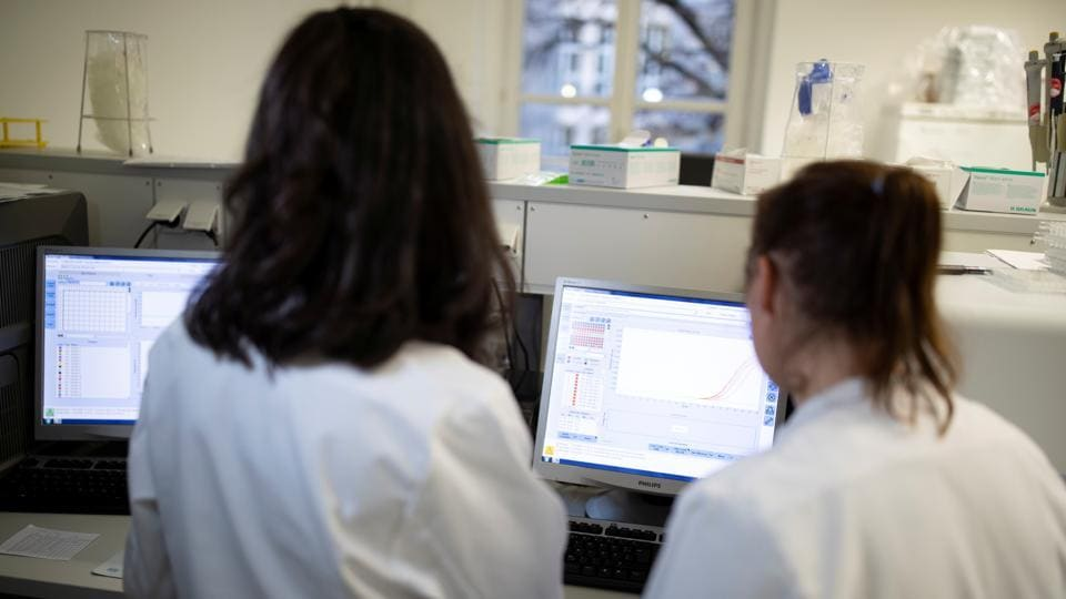 Employees of the virology department of the Charite hospital prepare a test for the new coronavirus in Berlin, Germany.