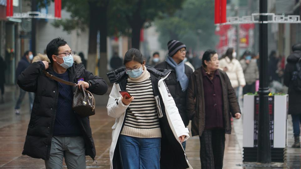 Masked pedestrians walk down a shopping street in downtown Wuhan, China January 22, 2020. The number of cases of a new coronavirus from Wuhan has risen over 400 in China and the death toll to 9, Chinese health authorities said Wednesday, Jan 22, 2020.