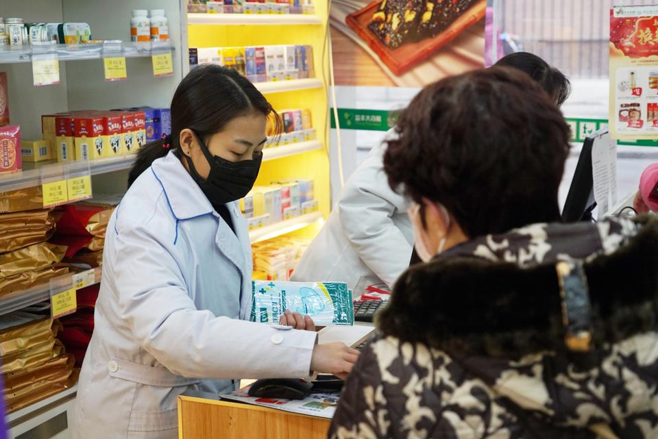 Staff sell masks at a Yifeng Pharmacy in Wuhan. Pharmacies in Wuhan are restricting customers to buying one mask at a time amid high demand and worries over an outbreak of a new coronavirus.