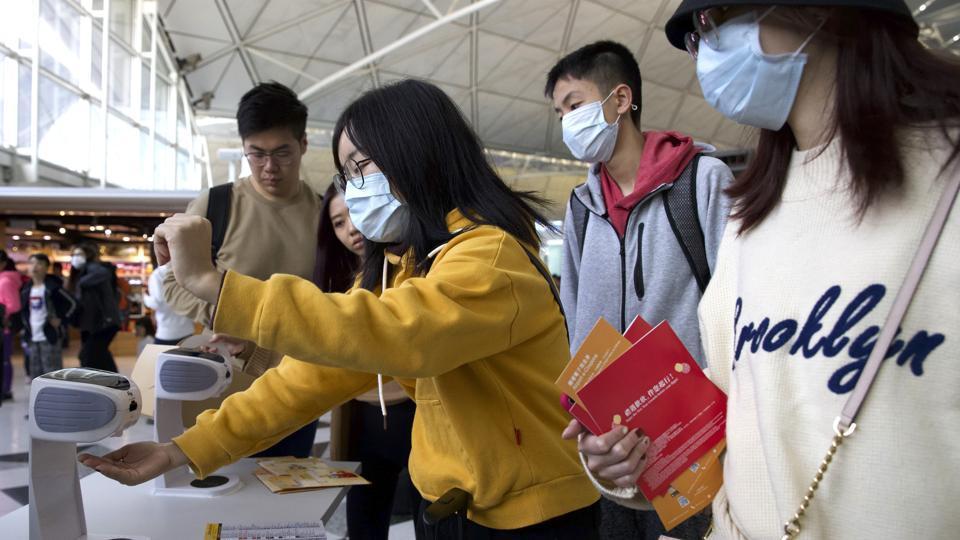 Travellers wearing face masks gather at Hong Kong International Airport in Hong Kong, Tuesday on January 21, 2020.