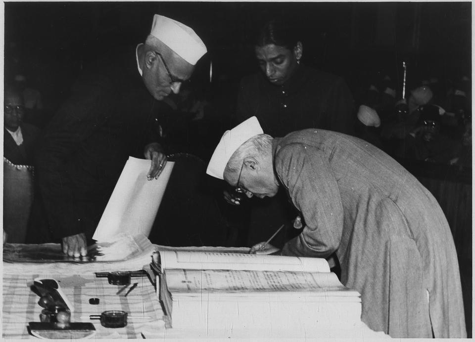 Jawaharlal Nehru signing the new constitution of India on 24 January, 1950, at the final session of the constituent assembly.