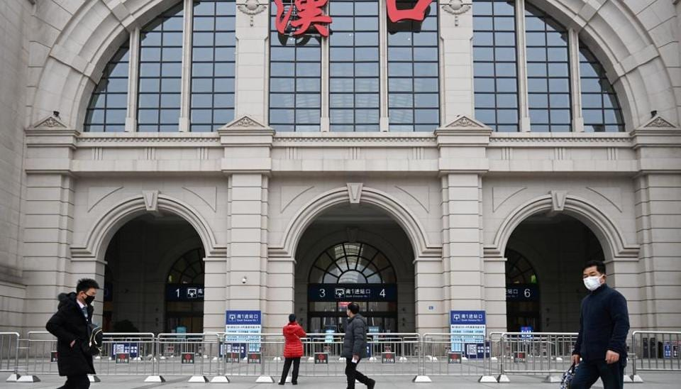People walk past the closed Hankou Railway Station after the city was locked down following the outbreak of a new coronavirus in Wuhan, Hubei province, China