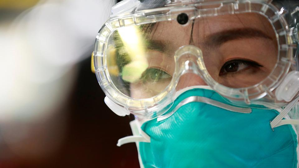 An official wears a protective mask and glasses as a measure to prevent the spread of coronavirus.