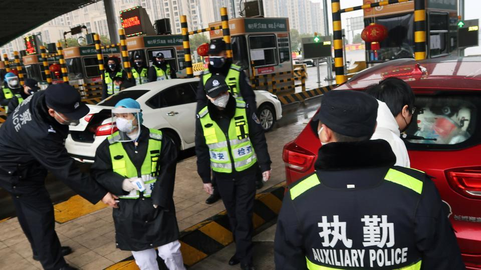 Police officers wearing masks check the boot of a car for smuggled wild animals following the outbreak of a new coronavirus, at an expressway toll station on the eve of the Chinese Lunar New Year celebrations, in Xianning, a city bordering Wuhan.