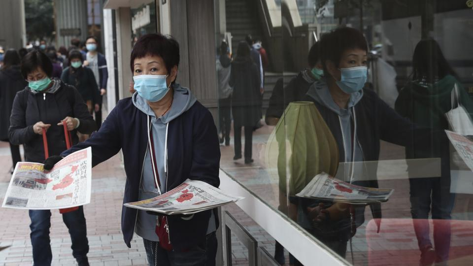 A woman wearing a protective face mask delivers a leaflet on coronavirus in Wuhan, in Hong Kong on Friday. China broadened its unprecedented, open-ended lockdowns to encompass around 25 million people to try to contain a new virus that has sickened hundreds.