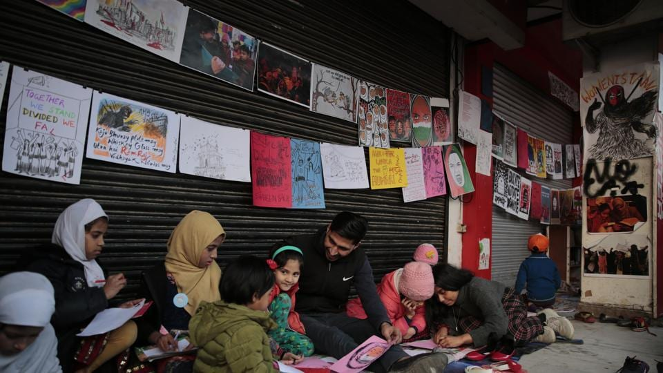 Young girls draw sketches near the protest site in New Delhi's Shaheen Bagh area, on Friday.