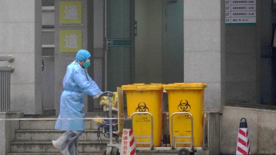 Staff moving bio-waste containers past the entrance of the Wuhan Medical Treatment Center, where some infected with a new virus are being treated, in Wuhan, China.