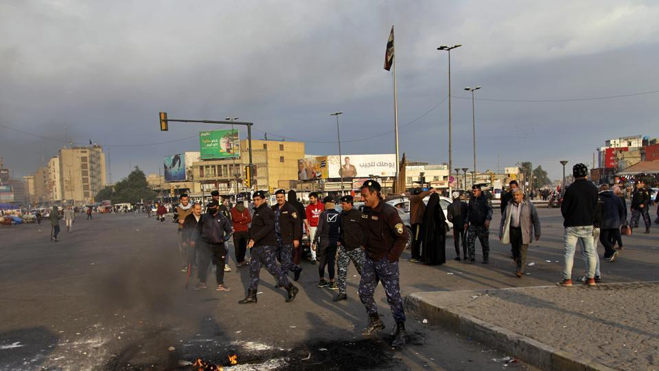 Security forces try to open streets while protesters set fire during a demonstration to protest against the Iranian missile strike, in Baghdad, Iraq, Wednesday, Jan. 8, 2020.