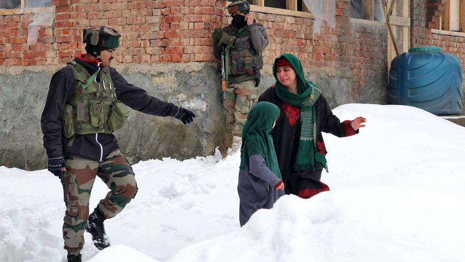 A woman walks past Indian soldiers near the site of a gun battle between suspected terrorists and security forces at Bathen village in south Kashmir's Awantipora.