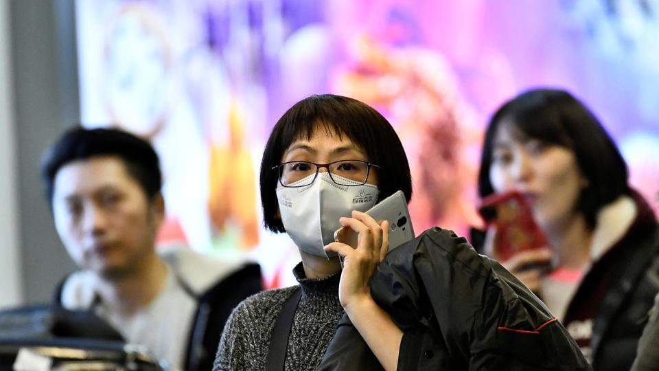 Travellers, wearing masks, arrive on a direct flight from China