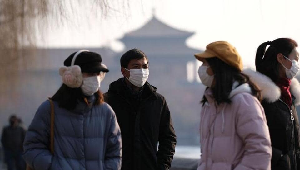 People wearing protective masks walk outside Forbidden City which is closed to visitors, according to a notice in its main entrance for the safety concern following the outbreak of a new coronavirus, in Beijing, China on January 25, 2020.