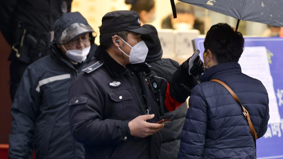 A policeman wearing a face mask takes a tourist's temperature at the Qinhuai scenic zone in Nanjing in eastern China's Jiangsu province.