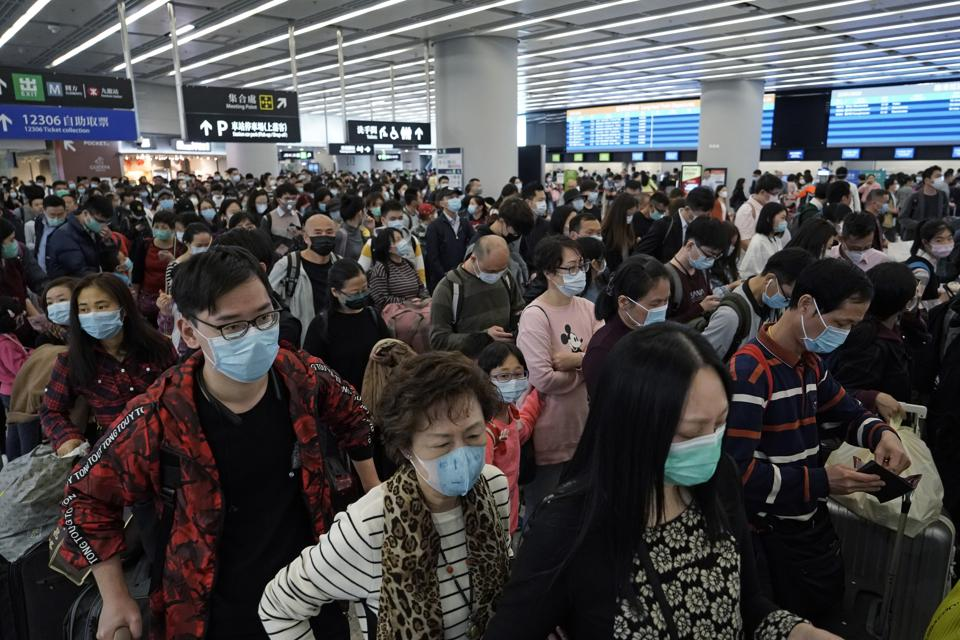 Passengers wear protective face masks at the departure hall of the high speed train station in Hong Kong.