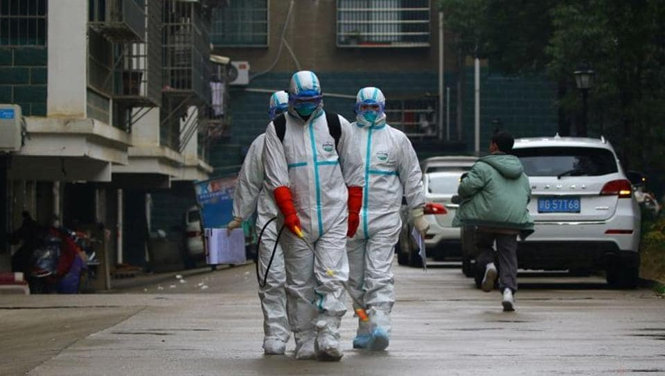 Workers from local disease control and prevention department in protective suits disinfect a residential area following the outbreak of a new coronavirus, in Ruichang, Jiangxi province.