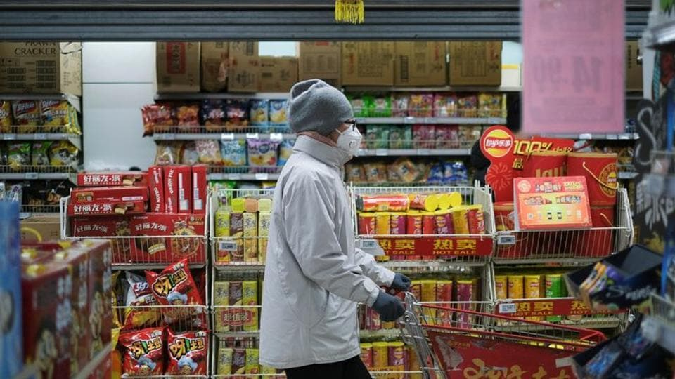 A woman wearing a face mask looks for goods at a supermarket, as the country is hit by an outbreak of the new coronavirus, in Beijing, China.