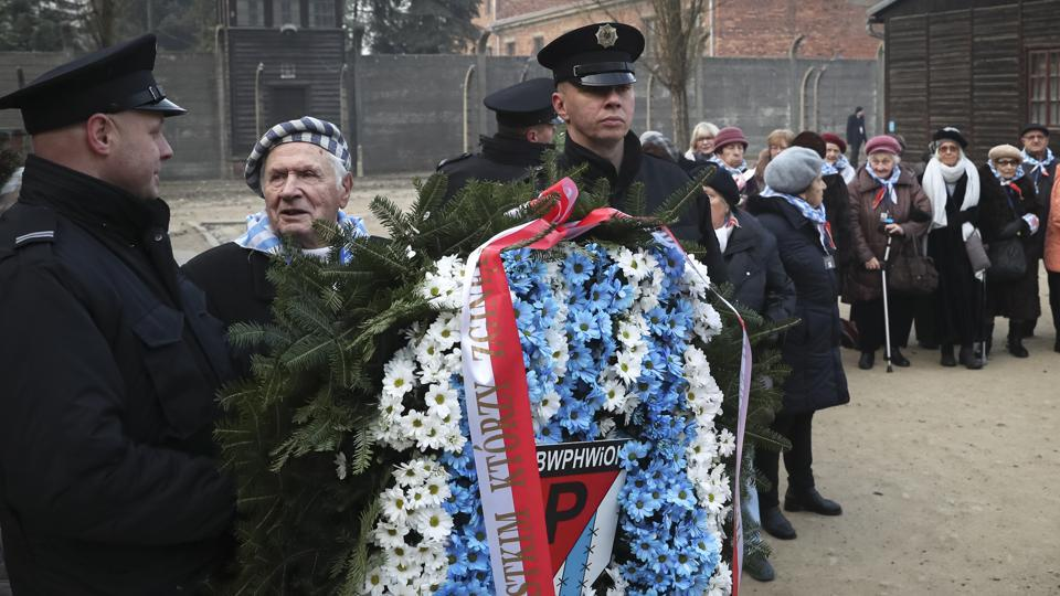 Survivors attend a wreath laying ceremony at the Auschwitz Nazi death camp in Oswiecim, Poland, Monday, Jan. 27, 2020. Survivors of the Auschwitz-Birkenau death camp gathered for commemorations marking the 75th anniversary of the Soviet army's liberation of the camp, using the testimony of survivors to warn about the signs of rising anti-Semitism and hatred in the world today.(AP Photo/Czarek Sokolowski)