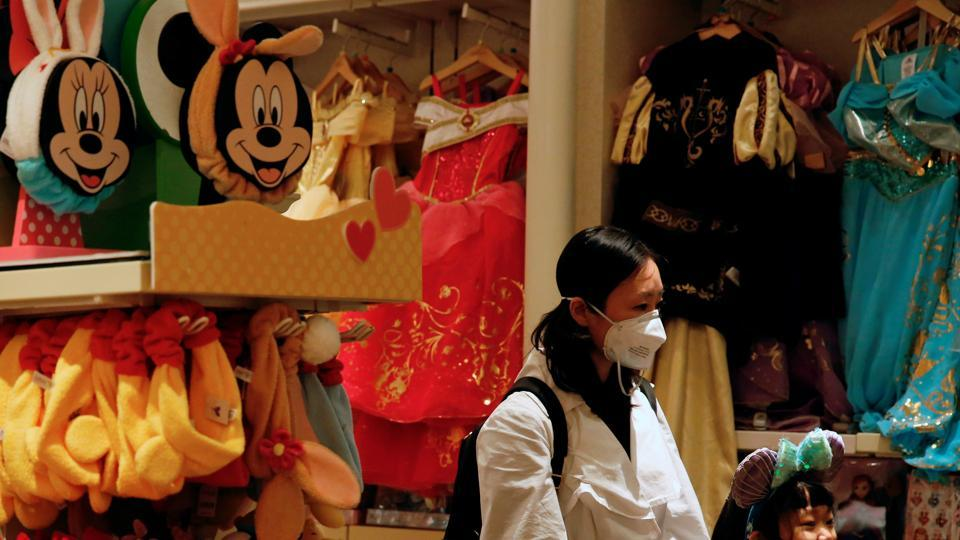 A child wears mask as she tries a themed ears at a souvenir shop in Disneyland hotel after Hong Kong Disneyland that has been closed, following the coronavirus outbreak in Hong Kong, China January 26, 2020.